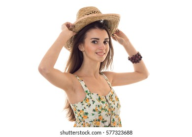 young cheerful woman in straw hat and sarafan with floral pattern smiling on camera isolated on white background