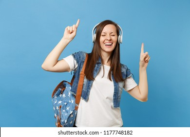 Young cheerful woman student with closed eyes with backpack, headphones listen music pointing index finger up dancing isolated on blue background. Education in college. Copy space for advertisement