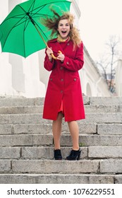 Young cheerful woman under an umbrella in the wind