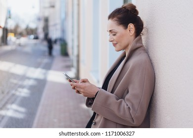 Young cheerful woman wearing grey coat using mobile phone in street