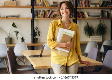 Young cheerful woman in yellow shirt leaning on desk with notepad and papers in hand joyfully looking in camera in modern office