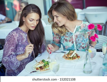 Young cheerful women on lunch at restaurant