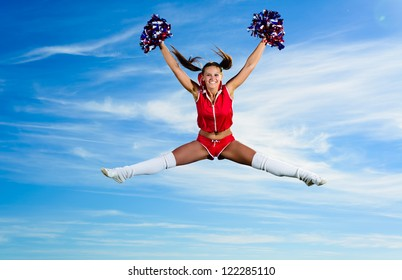 Young cheerleader in red costume jumping against blue sky