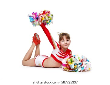 Young cheerleading girl with pompoms lying on the floor