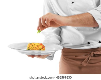 Young chef cook decorating dish isolated on white
