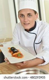 Young chef in cooking training school presenting dish