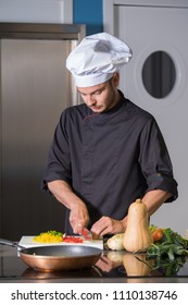 Young Chef cutting vegetables in a professional kitchen