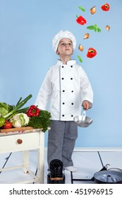 Young chef and his juggling with vegetables in a pan