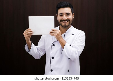 Young chef holding a white paper close to his head