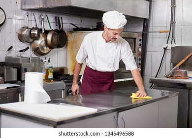 young chef in kitchen cleaning working table, after closing restaurant.