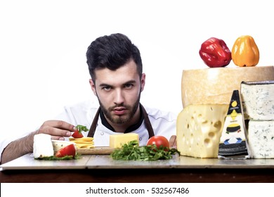 Young chef model cooks beneficial ingredients. The man in an apron builds the composition of cheese and greens