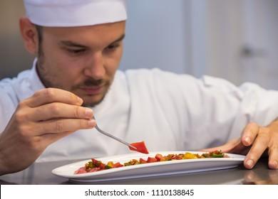 young chef plating a pork sirloin tartar