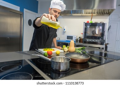 young chef pouring extra virgin olive oil to the pan in a professional kitchen