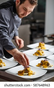 Young chef prepares delicious meals in restaurant kitchen.