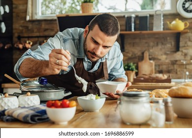Young chef preparing food and pouring dipping sauce into a bowl.