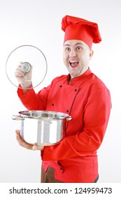 young chef in red on a gray background with a big pot in the hands of