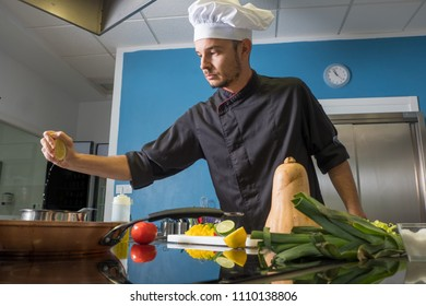 young chef seasoning his recipe with lemon