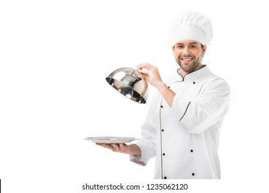 young chef taking of serving dome from plate isolated on white