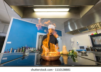 young chef vegetables flamed with fire in a frying pan, front view