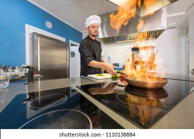 young chef vegetables flamed with fire in a frying pan, side view