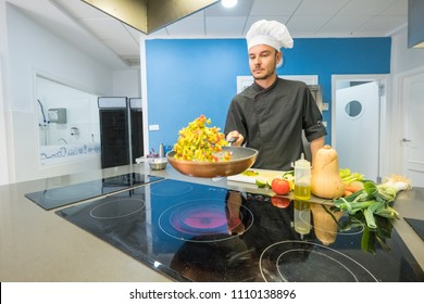 young chef sautéing vegetables in a professional kitchen