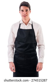 Young chef or waiter posing, wearing black apron and white shirt isolated on white background