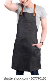 Young chef or waiter posing, wearing apron and gray t-shirt isolated on white background