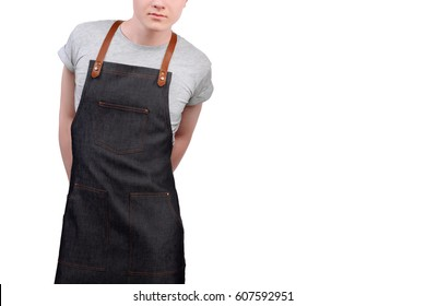 Young chef or waiter posing, wearing apron and gray t-shirt isolated on white background.