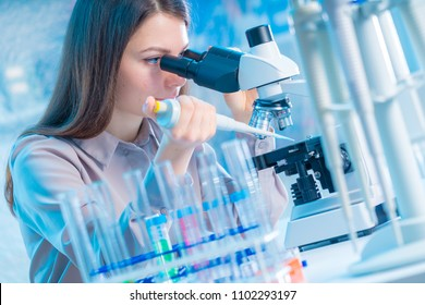 Young chemist in the laboratory. Scientist Using Microscope In Lab