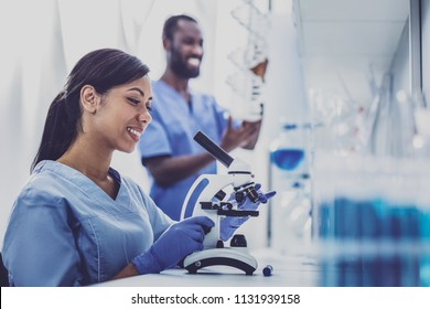 Young chemist. Professional young chemist feeling very inspired while using microscope sitting in modern laboratory