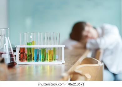 Young chemistry students sleeping after doing science experiment with equipment and wait reaction after mix chemical in laboratory, co-working of scientist concept.