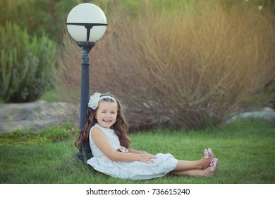 Young chestnut girl in white evening stylish dress posing close to park lamp smiling and enjoying vacation weekend sunday summer spring sunny day on green grass garden.