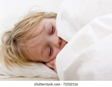 Young child, being sound a sleep, tucked in under his duvet