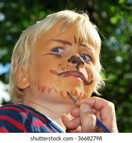 Young child being turned into a lion with make-up
