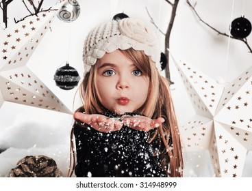 A young child is blowing white snowflakes in a studio background scene with stars and Christmas ornaments for a holiday concept.