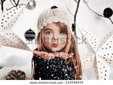 2272e3d5850b3 A young child is blowing white snowflakes in a studio background scene with  stars and Christmas