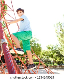 Young child boy climbing on climbing frame in park playground on sunny day, having fun smiling outdoors. Kid enjoying adventure playing activities, leisure recreation lifestyle.