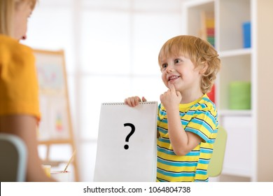 Young child boy holding drawing during therapy or lesson with woman