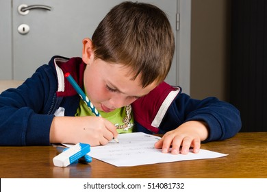 Young child (boy) learns to write and practices by writing letters and short words on a paper with a pencil