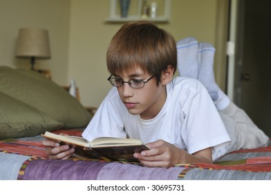 Young child boy reading a book on his bed