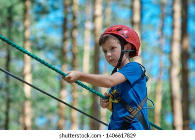 Young child boy in safety harness and helmet attached with carbine to cable moves confidently along rope way in recreation park.  Sport, game, leisure concept.