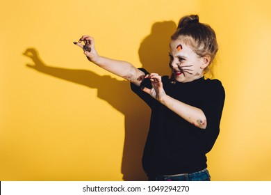 Young child with cat make up streching her hands. Playful child. Body painting.
