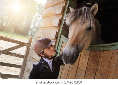 young child caucasian girl dressed in riding costume caressing a horse in a stable on a sunny summer day