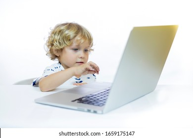 A young child with cheerful expression between 4 and 5 years old sitting at a desk while using a computer, in front of a white background.