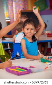 Young child at coloring table with raised hand