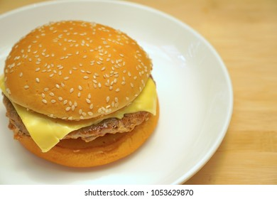 Young child cooking pork cheese burger on white plate. Fresh ingredient of pork, cheese, onion tomato. Simple style. Yummy.