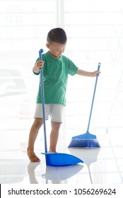 Young child doing house chores at home. Asian boy sweeping floor with broom.