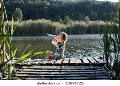 Young child explorer, girl-captain looks into the distance through a telescope at the lake at sunset, during summer vacation, happy family summertime concept, outdoor lifestyle