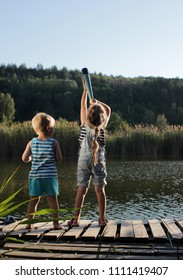 Young child explorers, boy-captain and his cute sister, look into the distance through a telescope at the lake at sunset, during summer vacation, happy family summertime concept, outdoor lifestyle