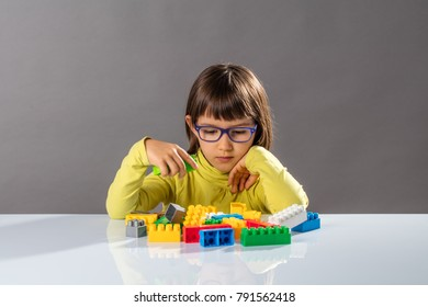 young child with eyeglasses learning in playing with building blocks, thinking about organizing toys with imagination, indoors